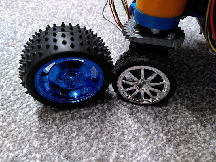 A detail view of a robot with small wheels next to larger spiked tires.