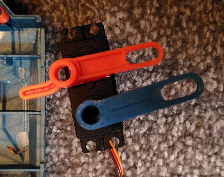 Custom printed trigger lever alongside the original orange one