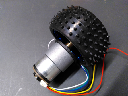 A metal geared motor and wheel assembly.